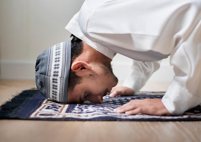 muslim man prostrating doing sajdah while praying